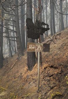 Blue River Reservoir sign burned around the edges in a burned forest.