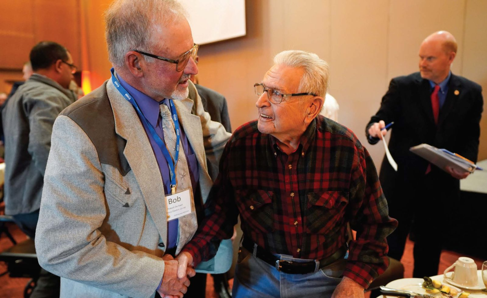 New Oregon Rural Electric Cooperative Association President Bob Durham, left, thanks Ben Asquith of Dayton, Oregon, for his service on D-Day. Asquith was an honored guest at ORECA's annual meeting in November