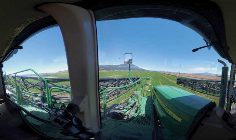 View from inside a tractor, looking at the field.