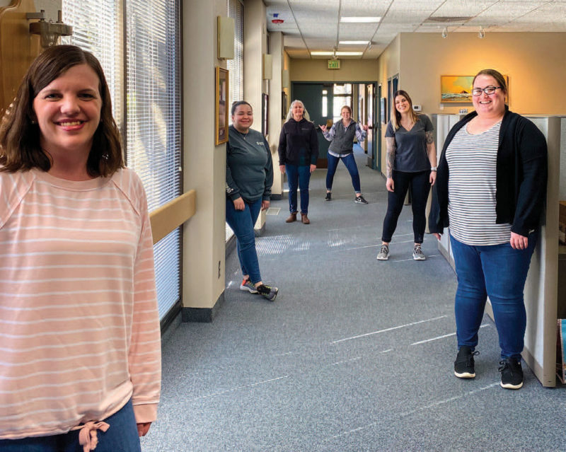 Six women standing down a hallway in an office, maintaining distance between them