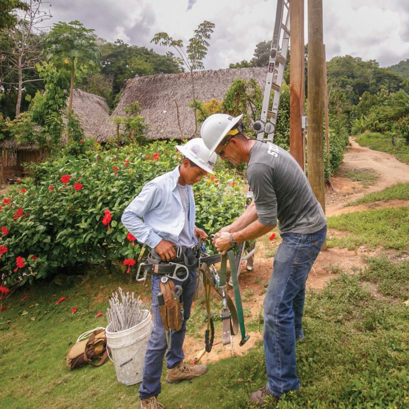 A lineman and local villager work on the Energy Trails Electrification Project in Guatemala
